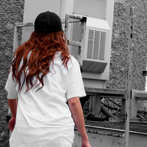 Back view of model wearing CONSUMED white t-shirt from PHOSIS Clothing