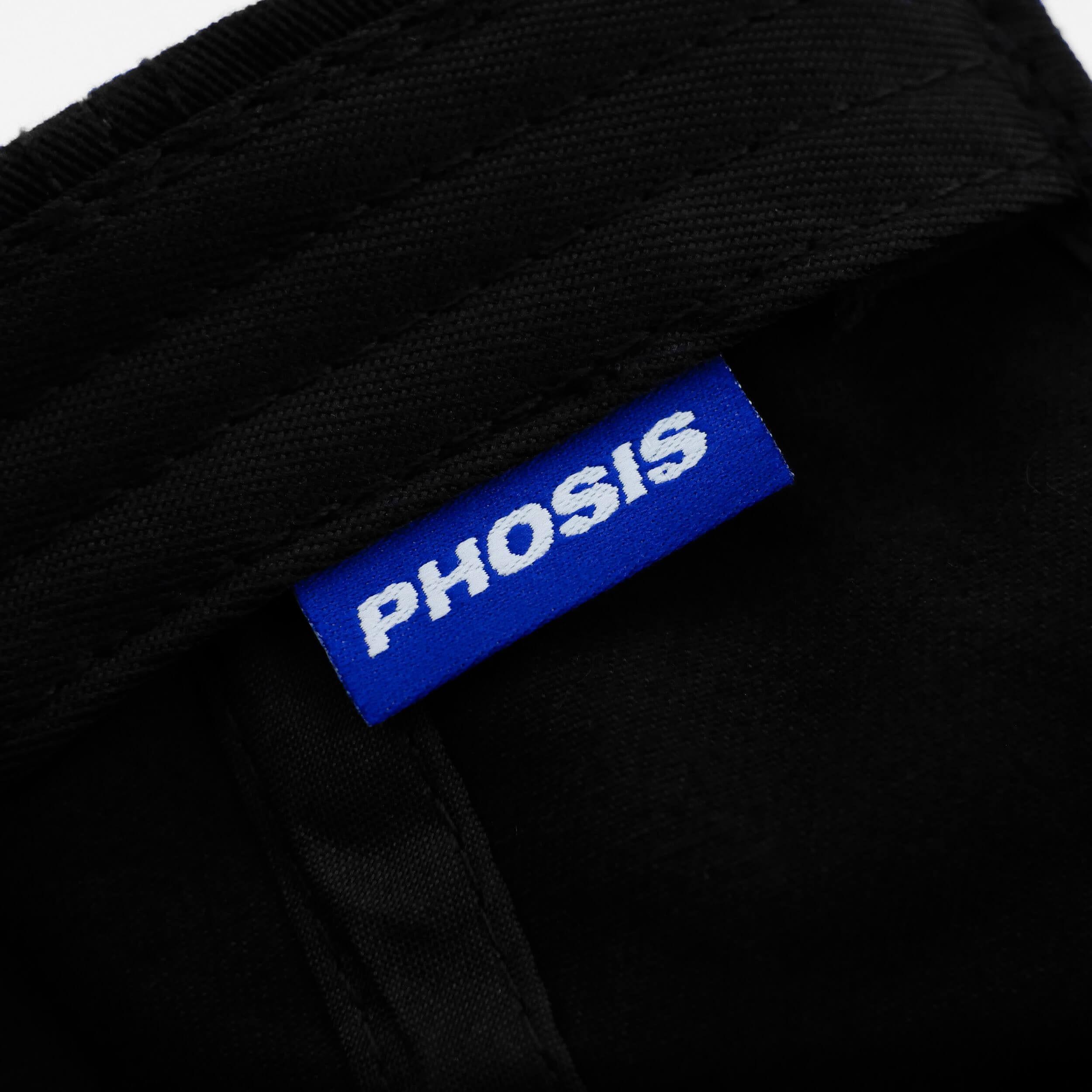 Close up view of the woven label in the 'FLAMBE' black dad hat from PHOSIS Clothing