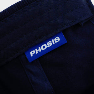 Close up view of the woven label in the 'FLAMBE' navy blue dad hat from PHOSIS Clothing