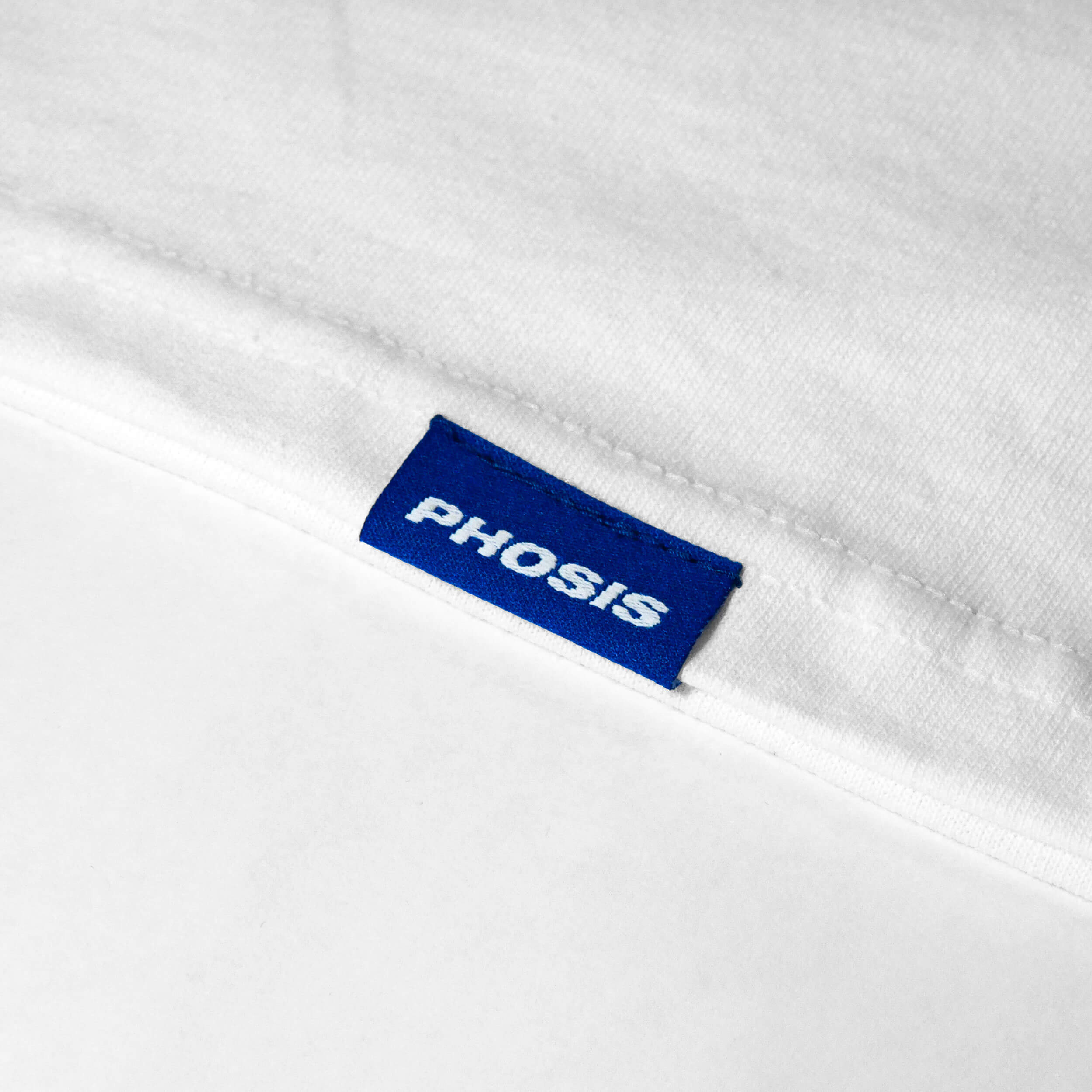 Close up view of the blue woven label in the POLYMER white long sleeve from PHOSIS Clothing