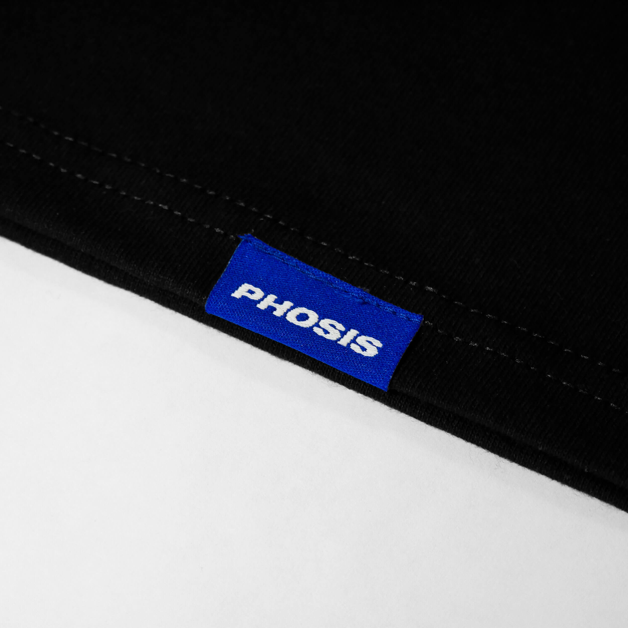 Close up view of the blue woven label in the SHOCK VALUE black t-shirt from PHOSIS Clothing