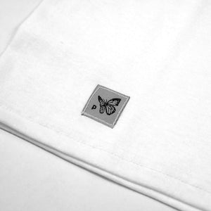Close up view of the grey logo tag in the CONSUMED white t-shirt from PHOSIS Clothing