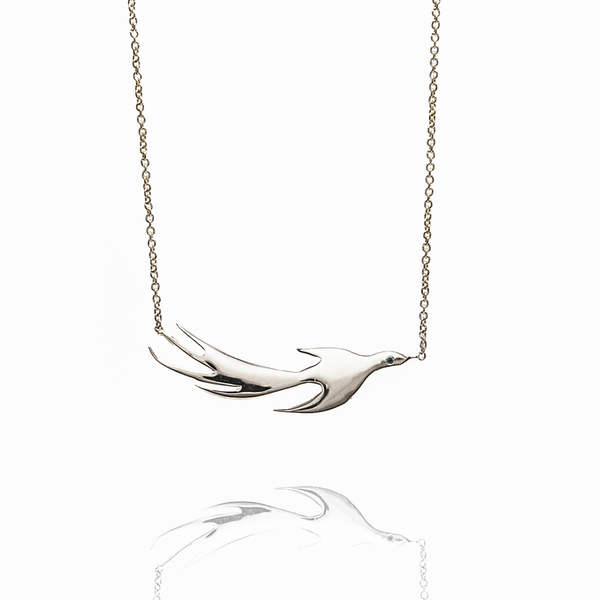 This phoenix necklace is a fierce, daily reminder of recreating ourselves and of wings spreading .  Sterling silver studded with a blue sapphire\ sensual Ruby .