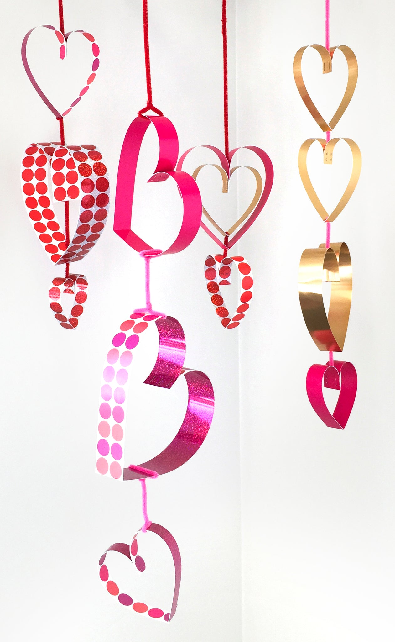 Easy DIY paper Valentine's Day hearts dangling decorations hang from ceiling