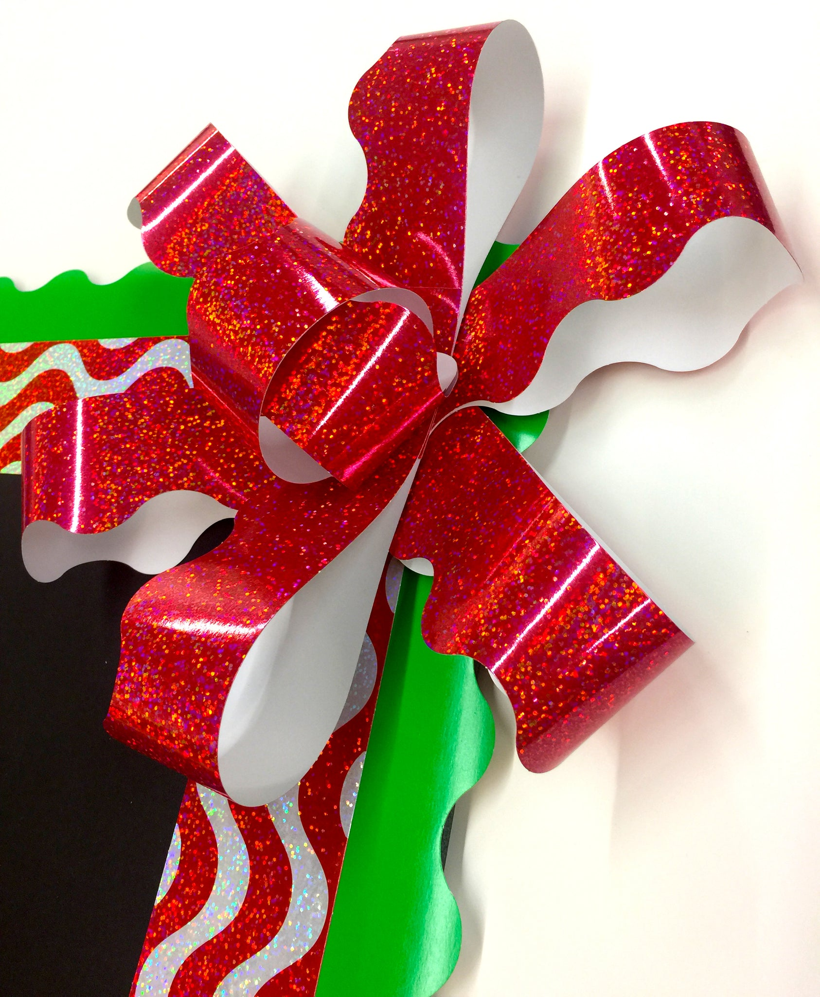 Big red sparkle paper bow for Christmas bulletin board. DIY how to make a paper bow.