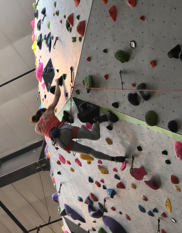 a Colorado woman scales the rock at the climbing gym