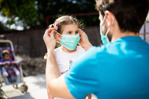 Father putting mask on daughter, Getty Image, How to enjoy the holidays with COVID