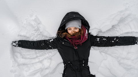 Woman making snow angels in snow.