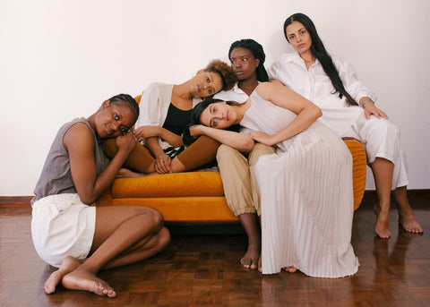 Five women, of multicultural backgrounds, sitting on an orange sofa. Image by Retha Furguson