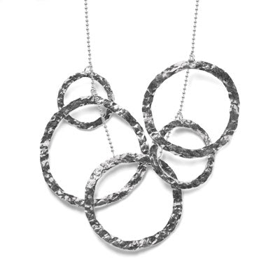 The five silver rings is hand-hammered; arranged asymmetrically, they hang together on a classic ball chain. The overall effect is thoroughly contemporary: a balance of bold graphic statement and delicate, organic texture.  MATERIALS | Hand hammered silver and ball chain.  SIZE | Large circle is 60 mm, 50 mm, 35 mm, 30 mm. Length is 28″