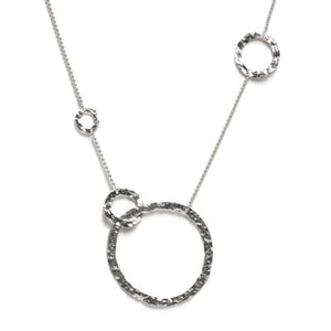 The Balance necklace presents four asymmetrically scattered hand-hammered silver rings along a classic ball chain to achieve a simple, exquisite balance of shape and texture. It's for the confident woman. Hand-hammered silver and silver ball chain. The large circle is 60 mm, 25 mm, 20 mm, 15 mm. Length is 26″