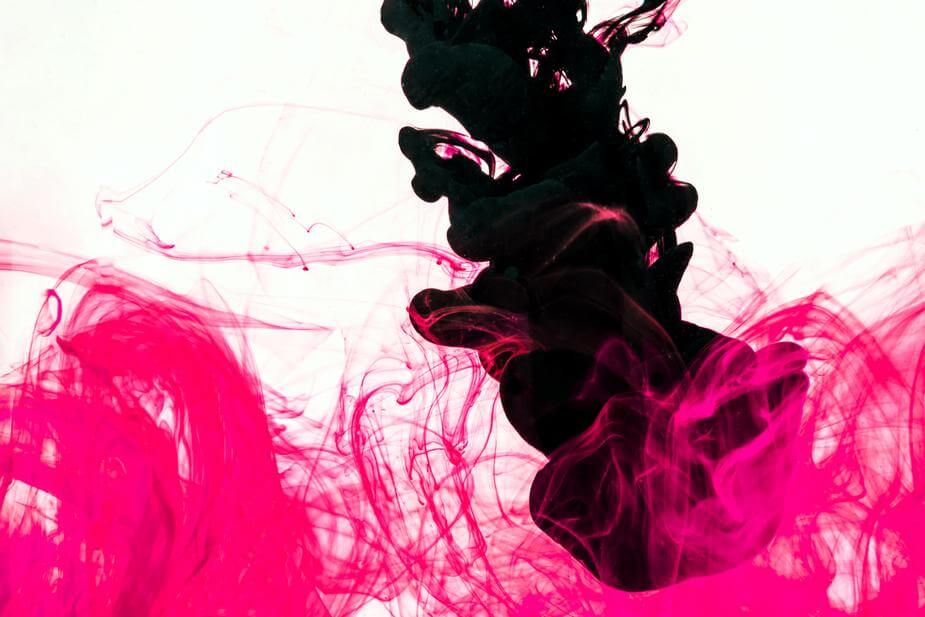 A jet of black ink mixes together with thin wisps of pink ink
