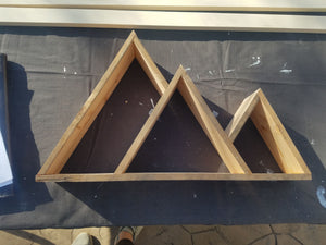 This mountain shelf has a series of descending mountain peaks. It was built outside in the sunny colorado weather out of reclaimed 2x4s planned down to a thin yet sturdy width.