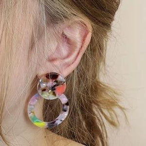 multicoloured resin earrings in ear