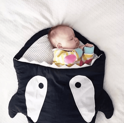 Image of a baby sleeping inside the mouth of a sleeping bag shark.