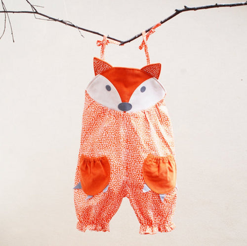 Picture of a Safe Haven Baby romper hanging from a tree branch. Features an orange fox head and paw pockets.