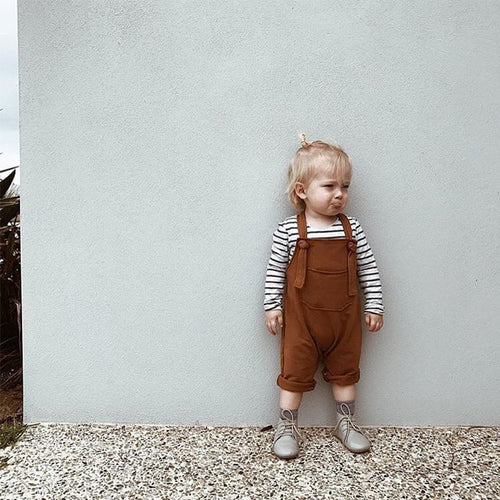 Picture of a toddler in rust-colored overalls standing in front of a blank wall.