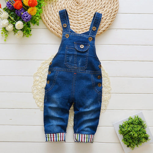 Image of baby-sized navy blue, denim overalls with rainbow stripes on the ankle cuffs.