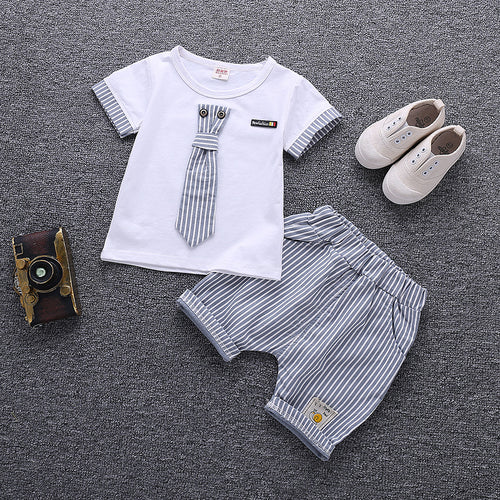 Picture of a T-shirt with a striped tie on the shirt. T-shirt is beside matching striped shorts.