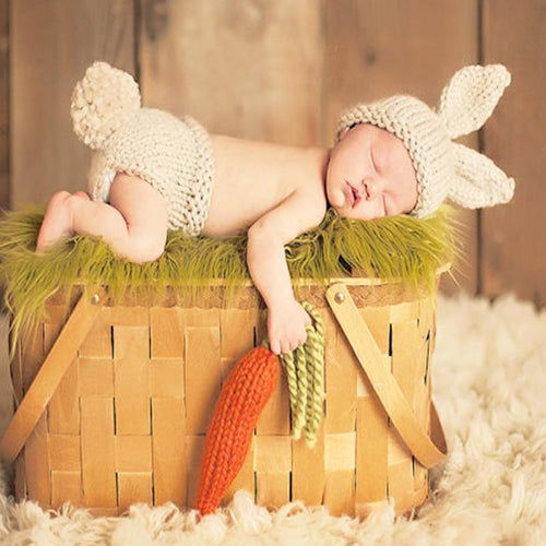 Image of a newborn sleeping on their stomach on top of a picnic basket. The baby is wearing a cream-colored knit hat with rabbit ears and a cream colored knit bottom with a puffy rabbit tail.