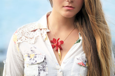 A large gold vase Fleurings necklace that holds water and fresh flowers worn with red vanda orchids. Designed by Samantha Lockwood. Modeled by Alayna McGuiness on the Big Island of Hawaii.
