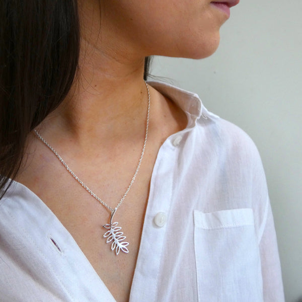 Girl wearing silver fairy tree pendant