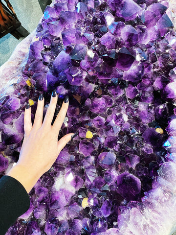 A hand on a giant amethyst cluster