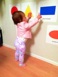 toddler pointing to shapes filled with primary colors