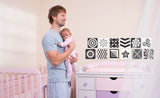 father holding baby with black & white repositionable decals on wall