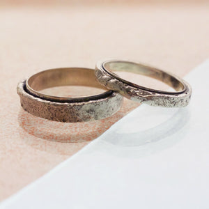 Two matching wedding bands, the slimmer band rests on top of a thicker band. Both a beautiful and unusual with a polished thin inner band and a rough, raw textured outer band. Made in oxidised recycled sterling silver.
