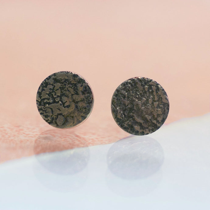 A pair of full moon stud earrings with ear sticks. Rough raw organic texture on flat round earrings. The silver is oxidised so the texture is accentuated in with black on the silver. handmade with a moonscape texture to resemble the surface of the moon. Made in Copenhagen by Scottish designer Caroline Cloughley.