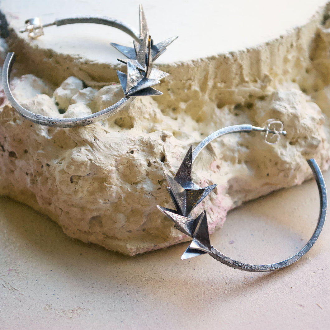 A pair of hoop earrings covered in little silver origami folded planes. The hoops have a rough, rustic, raw texture and are oxidised to look black. Handmade in recycled silver in Copenhagen by Scottish artist Caroline Cloughley.