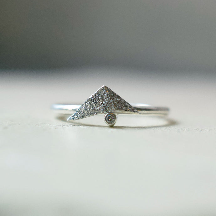 Beautiful unusual diamond ring. A folded silver triangle sits on top of a champagne diamond. The folded triangle is made in recycled sterling silver and has a rough, raw, rustic, organic texture. The ring has a delicate slim band. Handmade in Copenhagen by Scottish artist Caroline Cloughley.