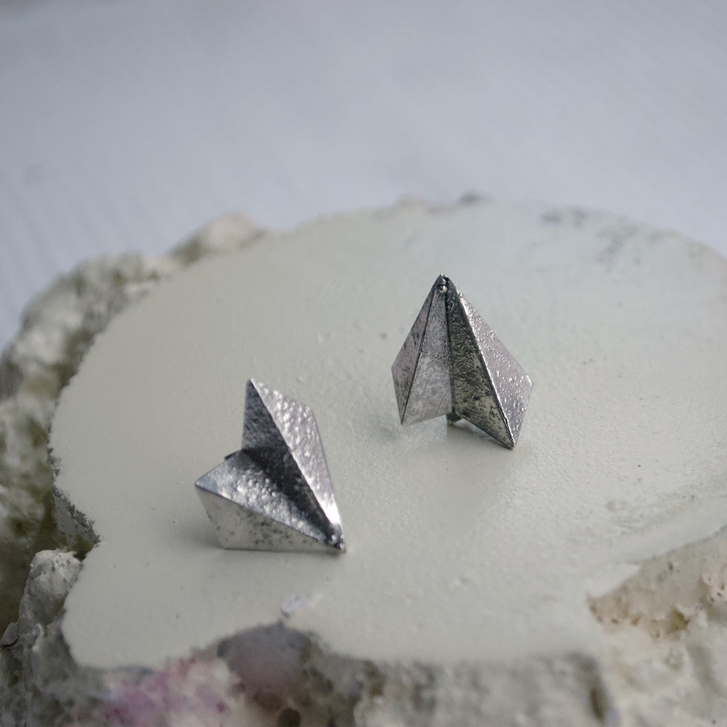Handmade, fan shaped geometric stud earrings. Origami paper style with rough, raw rustic, surface texture. Made in Copenhagen recycled silver.