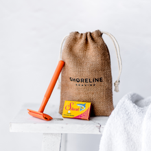 Load image into Gallery viewer, Orange Reusable Safety Razor leaning on a hessian bag with a white towel in the foreground - Shoreline Shaving