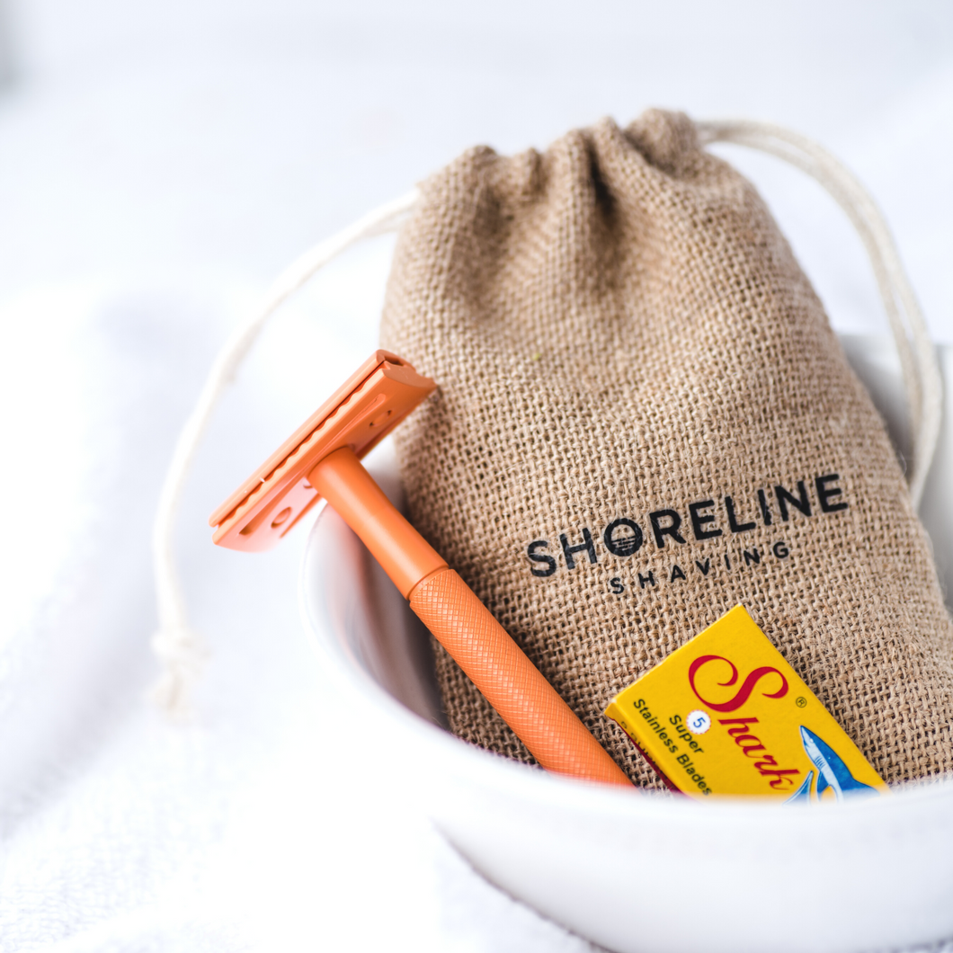 Orange Safety Razor with blades and hessian bag in a white bowl - Shoreline Shaving