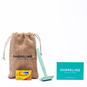 Mint green safety razor with blades, hessian bag and branded card on a white background - Shoreline Shaving