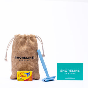 Pale blue safety razor with blades, hessian bag and branded card on a white background - Shoreline Shaving