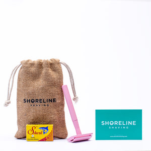 Pastel pink safety razor with blades, hessian bag and branded card on a white background - Shoreline Shaving