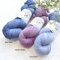 3 skeins of 8 ply knitting yarn in light blue lavender and dark blue on a white background with plant