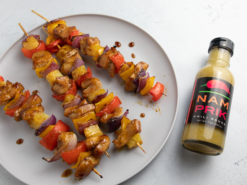four chicken skewers on a plate with a bottle of nam prik chili sauce