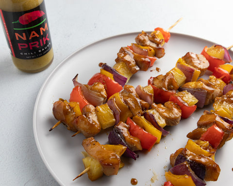 a plate of teriyaki chicken skewers with a bottle of nam prik chili sauce