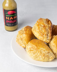 a plate of empanadas with a bottle of nam prik chili sauce