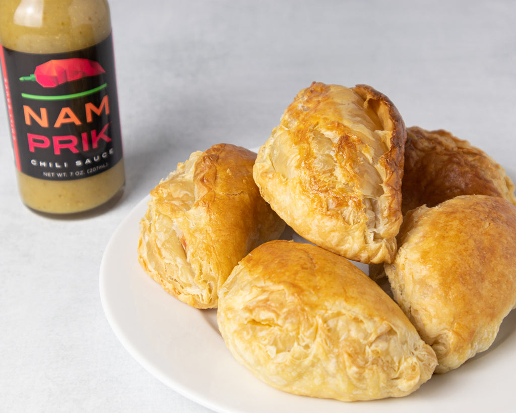 empanadas on a plate with a bottle of nam prik chili sauce