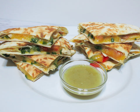 Two stacks of freshly cooked chicken quesadilla with a sauce dish of Nam Prik Chili Sauce
