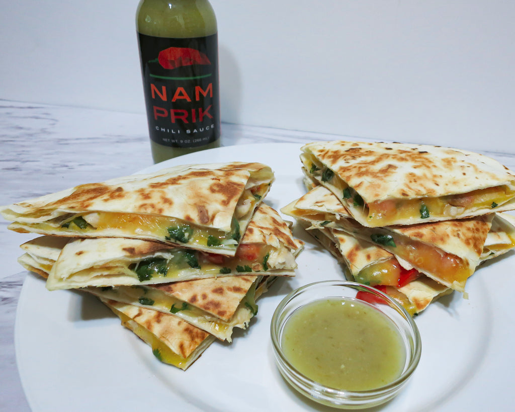 Two stacks of chicken quesadilla with a bottle of Nam Prik Chili Sauce in the back