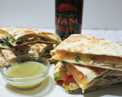 Two stacks of chicken quesadilla with a bottle of Nam Prik Chili Sauce behind