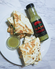 Overhead shot of chicken quesadillas and Nam Prik Chili Sauce next to them
