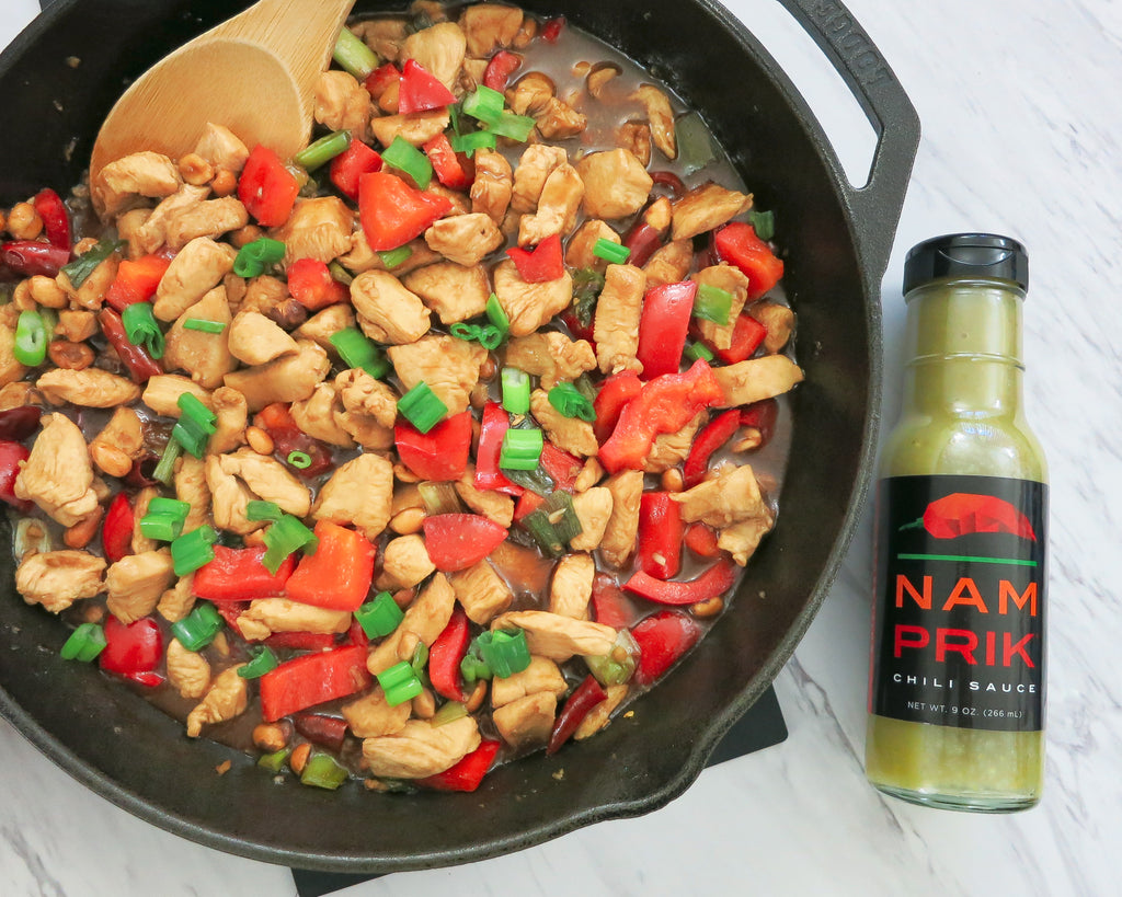 kung pao chicken in cast iron skillet and a bottle of nam prik chili sauce