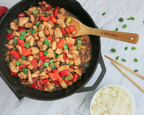 cooked kung pao chicken in cast iron skillet, a bowl of rice, and a pair of chopsticks